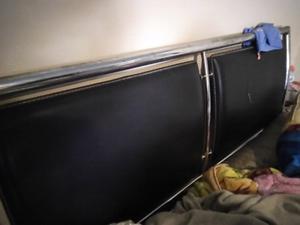 cama con cabecera negro con un par de cajones y cajones con
