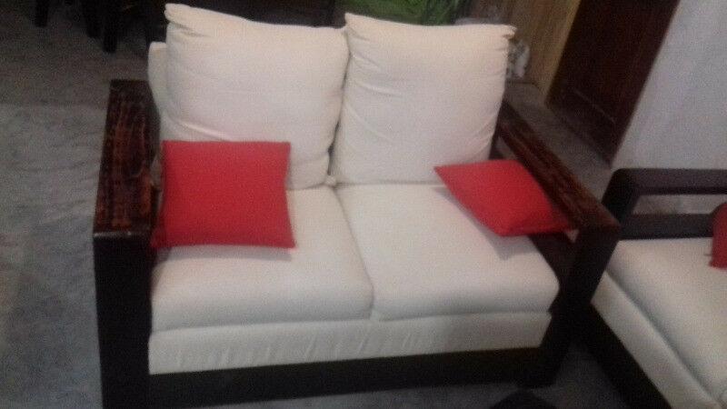 Sala con dos sillones de dos plazas cada uno y taburete