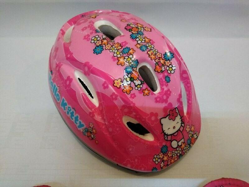 Hermoso casco, rodilleras y coderas de ciclista para niña